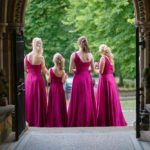 Bridesmaids in purple dresses await their bride in the beautiful doorway of Wentworth Church in Rotherham, near Sheffield. Wedding photographer is inside looking outwards.