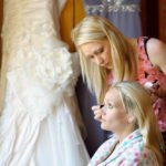 Wedding photograph of a bride having her make up done at Wortley Hall in Sheffield. The dress hangs in the background.