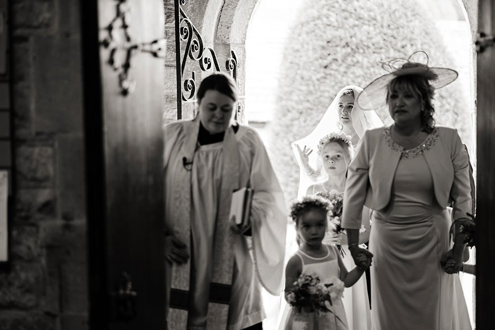 Black and white wedding photography for training wedding photographers. A bride enters a Derbyshire church