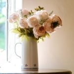 Pink roses in a rustic jug at a wedding