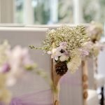 Detail shot of wedding flowers on the side of a chair from a wedding at Lee Wood Hotel in Buxton, Derbyshire