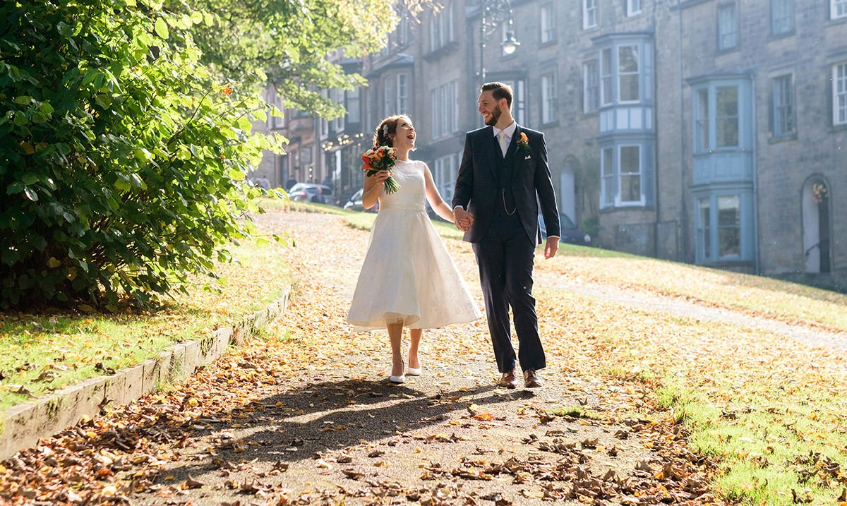 After their wedding at Buxton Church, a bride and groom admire each other in the evening sunlight on the lane near Losehill House. A perfect location in the Peak District for their wedding photography.