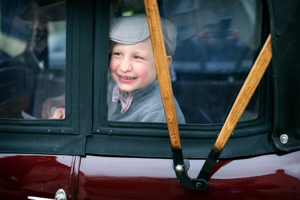 page boy looking out of the window of a vintage car on the way to a church wedding in the Peak District. Photograph by Sheffield wedding photographer, John Mottershaw.