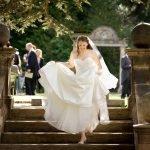 A bride walks down the garden steps at her wedding at Thornbridge Hall in Derbyshire