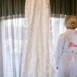 bride looks at her dress before getting ready for her wedding at Peak Edge Hotel in the Derbyshire Peak District