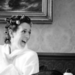 humorous wedding photograph. The bride laughs as she gets ready for her wedding at Whitley Hall