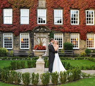 Bride and groom pose for their wedding photographer in front of Whitley Hall in Sheffield