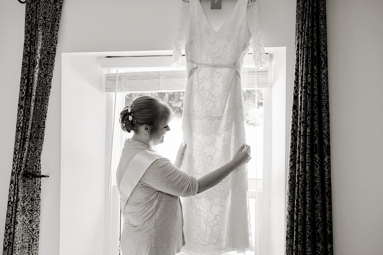 wedding photographer at Losehill House in the Derbyshire Dales. The bride admires her dress.