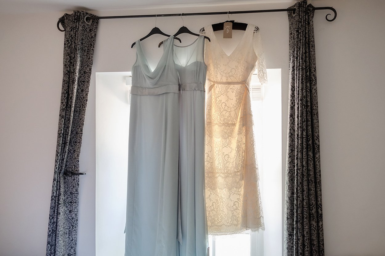 Photograph of wedding dresses hanging in the window