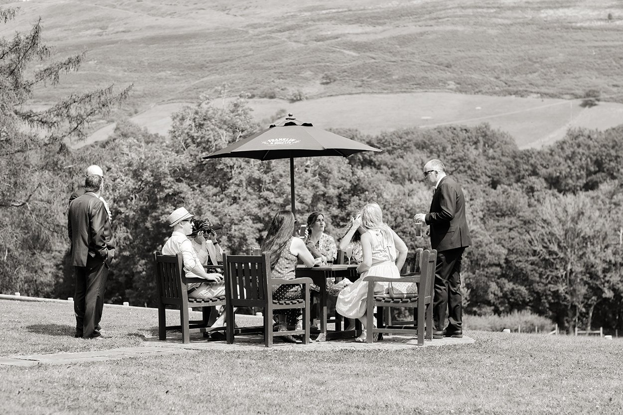Black and white photograph of guests outside at a wedding at Losehill House in the Derbyshire Peak District