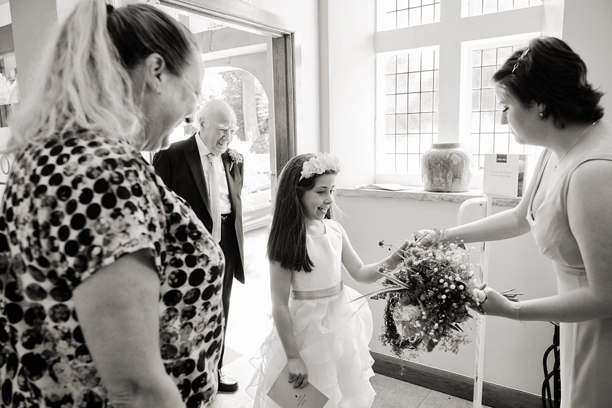 A bridesmaid arrives ready for her duties. Reportage wedding photography.