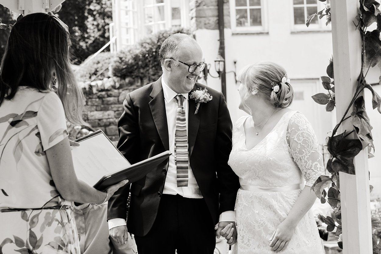 Black and white wedding photography as a bride arrives at her outdoor wedding.