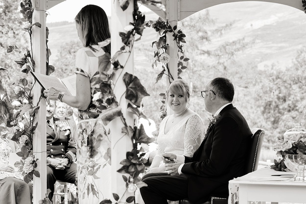 Black and white wedding photography: a bride looks at her groom during an outdoor ceremony in the Derbyshire Peak District. You can see the hills in the background.