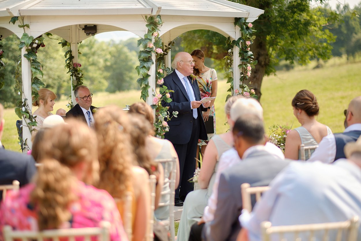 The bride's father during his reading at a summer wedding ceremony outdoors.