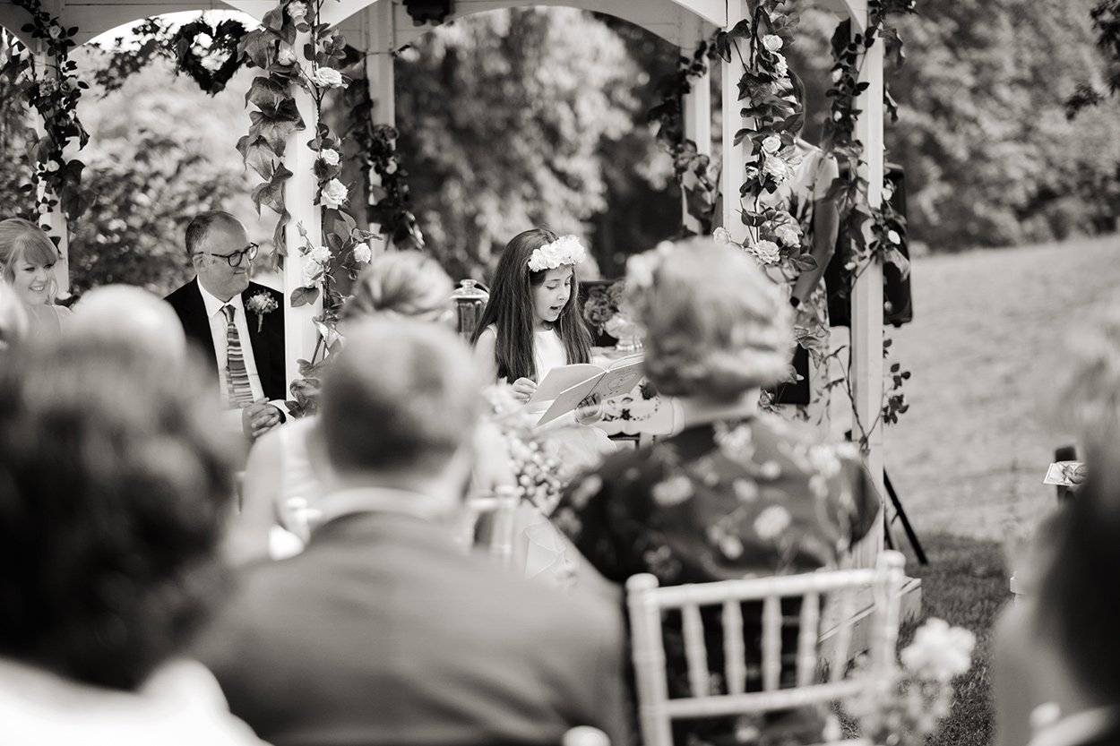 Bridesmaid reading at an outdoor wedding ceremony.