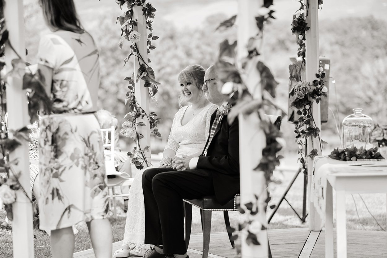 balack and white shot of a couple seated at their outdoor Humanist wedding ceremony