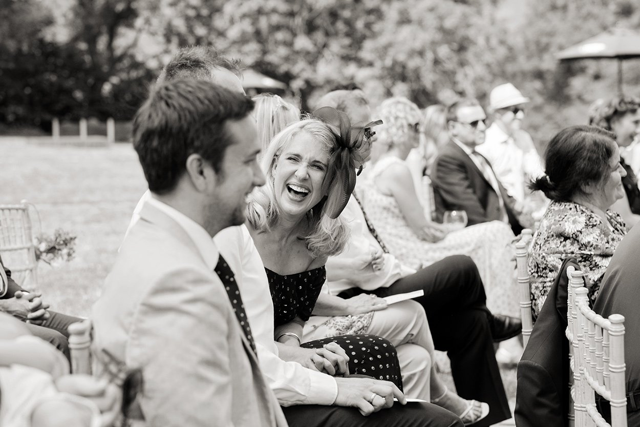 Black & white photograph of wedding guests laughing. Reportage.