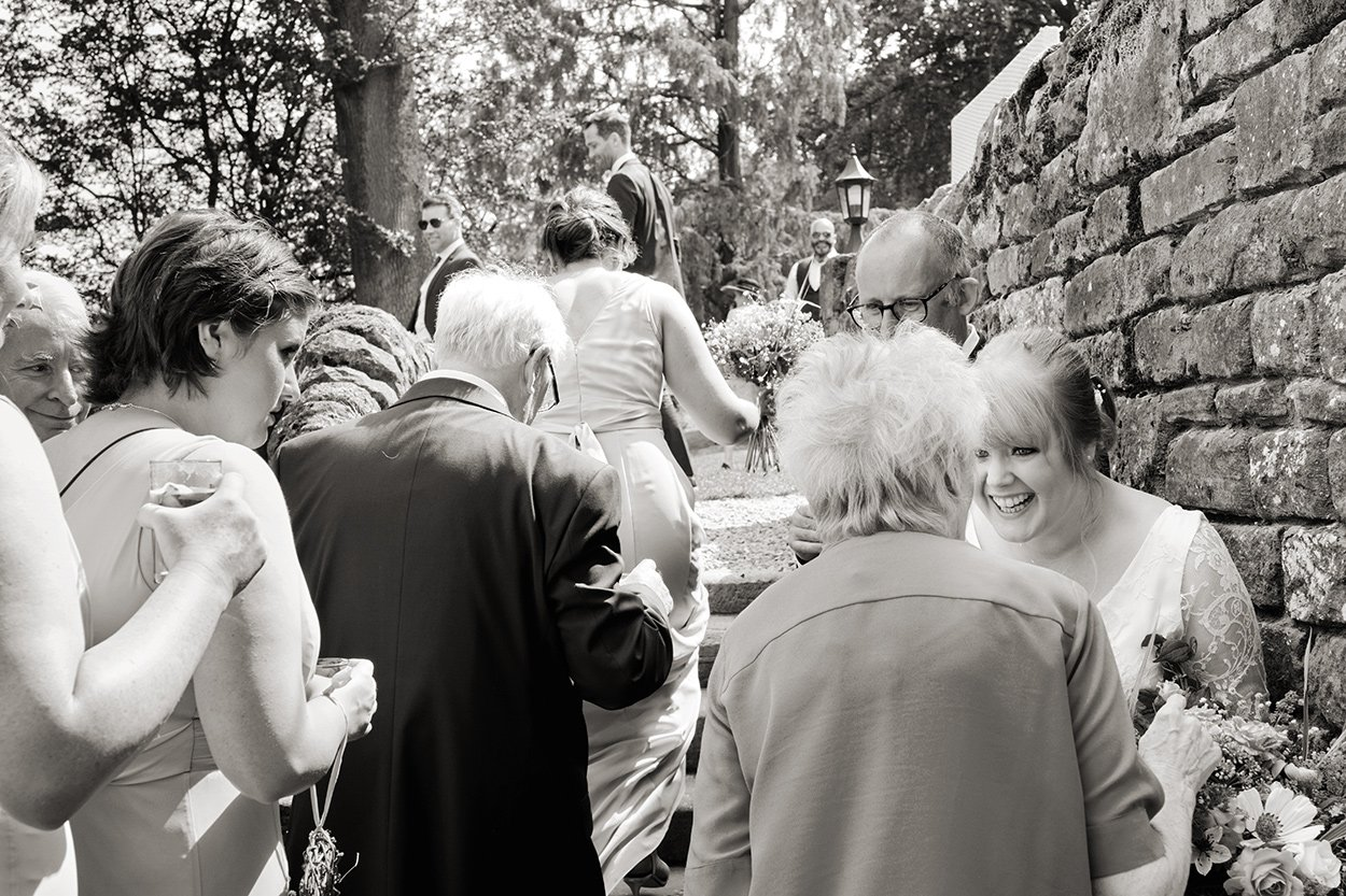 Bride chats with a guest on this informal reportage black and white wedding photograph