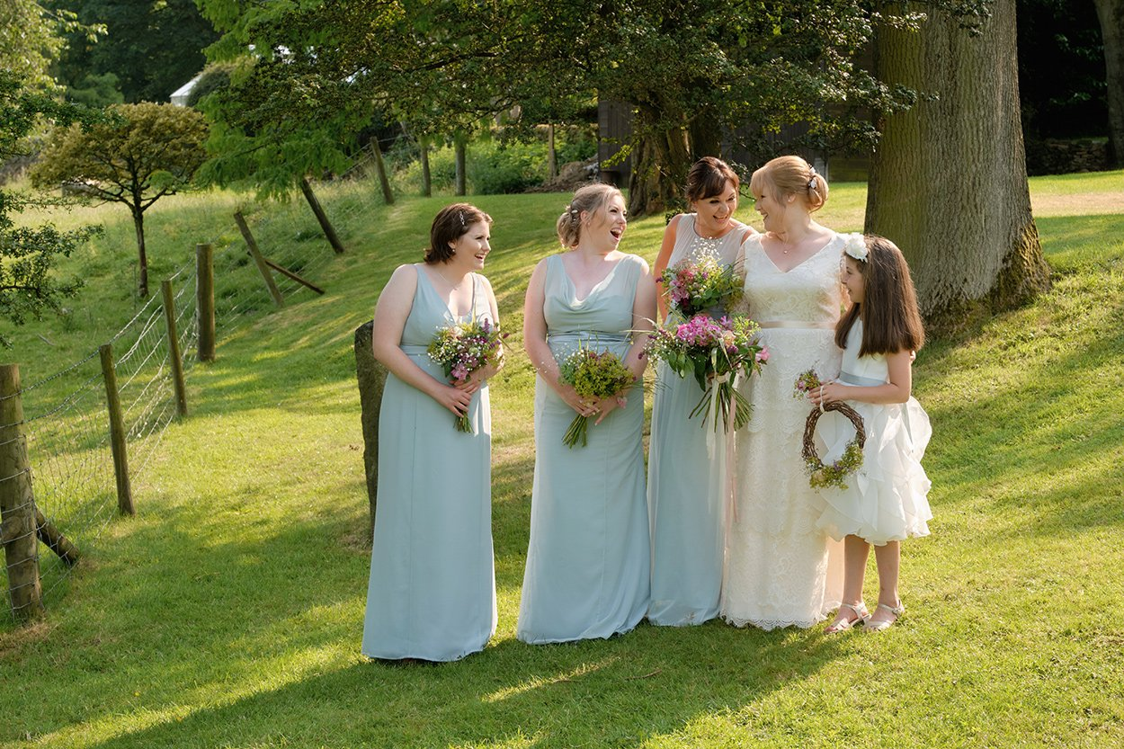 Bridesmaids and bride chatting and joking after a wedding at Losehill House.