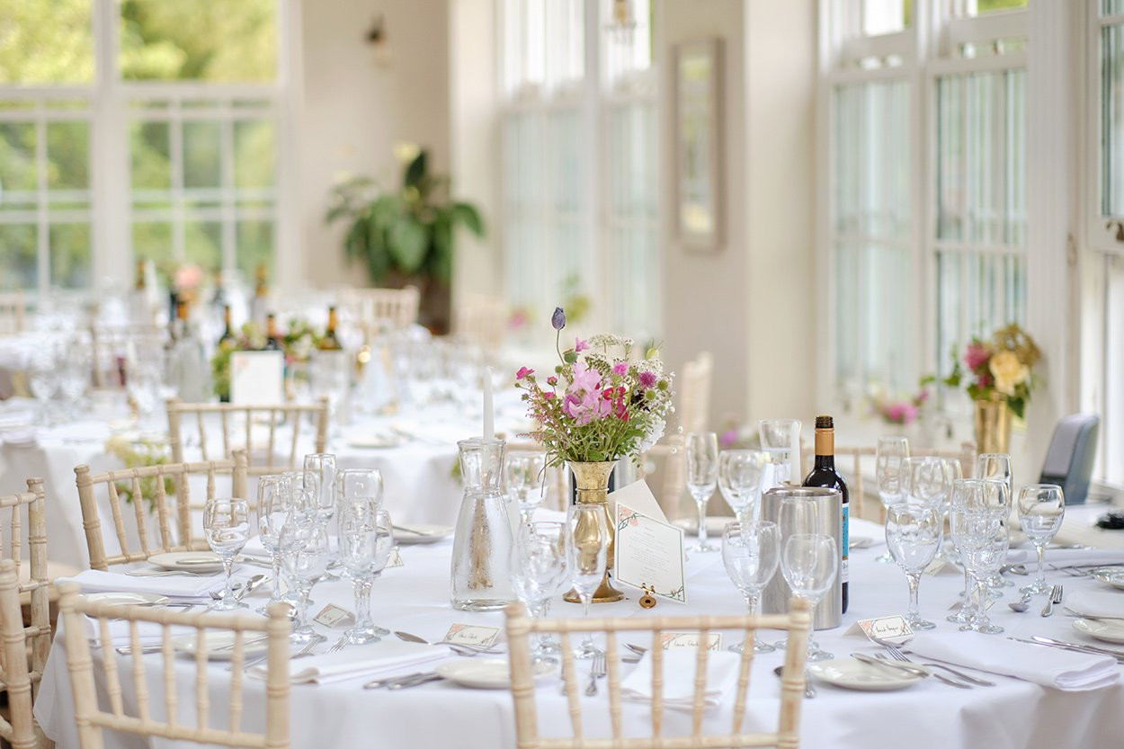 Table laid out at a summer wedding breakfast in the orangery at Losehill House