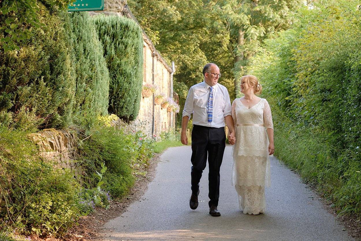 bride and groom walk along the country lane after their wedding at a Derbyshire country house