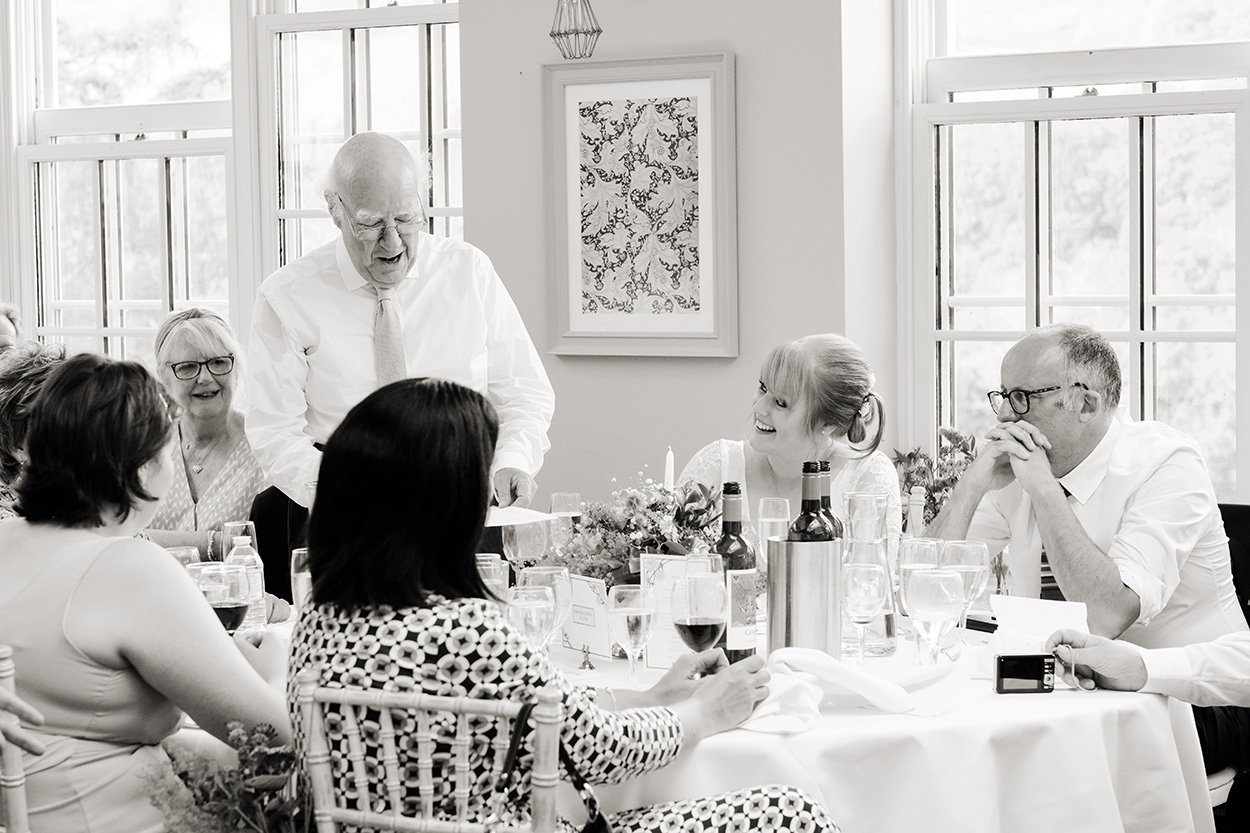 Black and white wedding photography: a bride looks at her father as he makes his speech at Losehill House