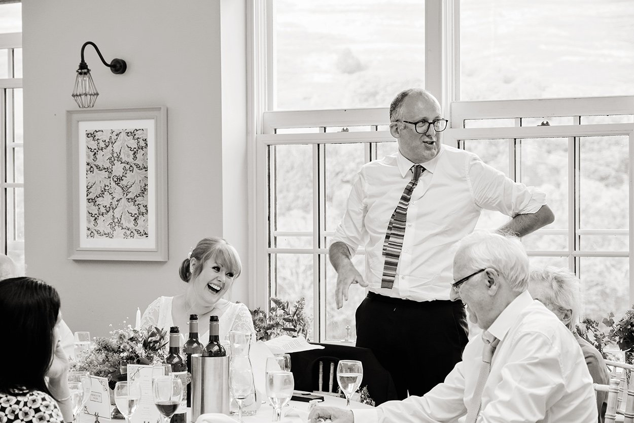 Black and white wedding photography: a bride looks at her groom , laughing, as he makes his speech