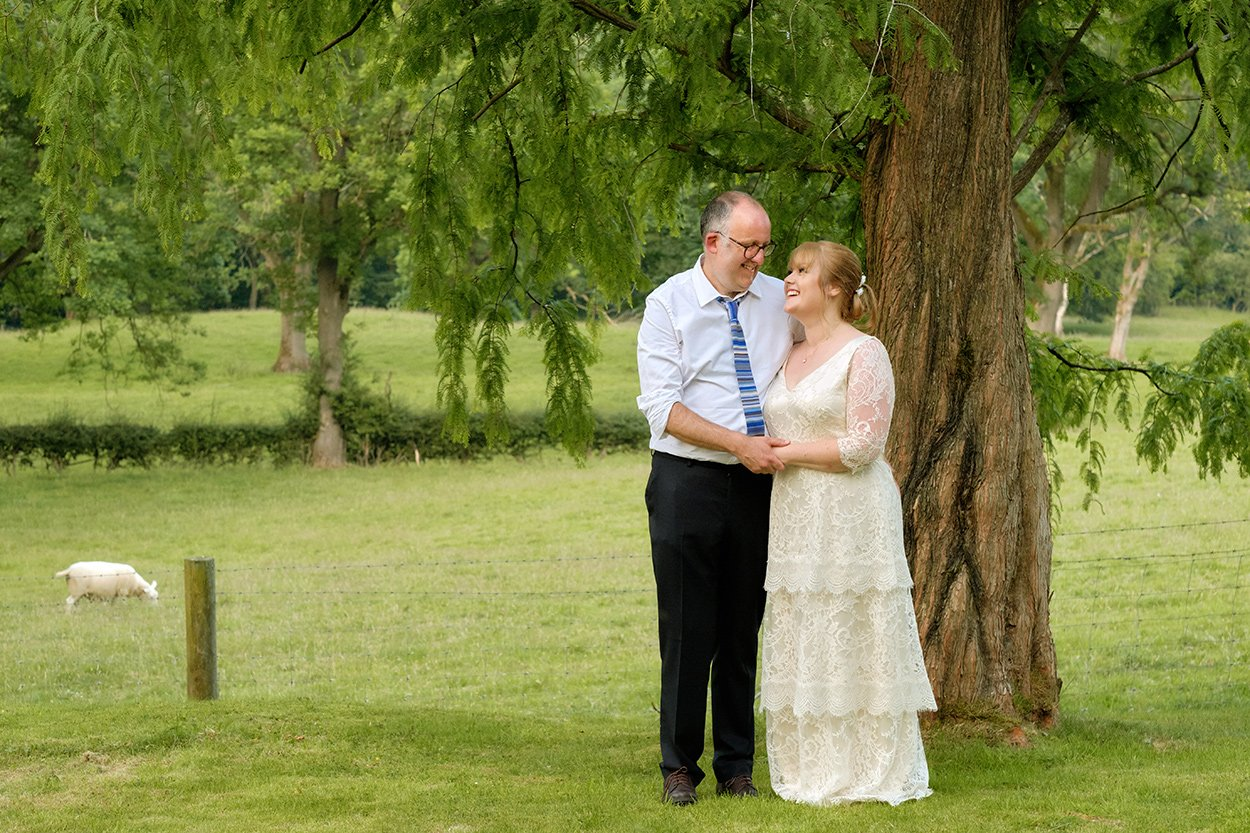 A bride and groom pose by a tree at a rural wedding reception